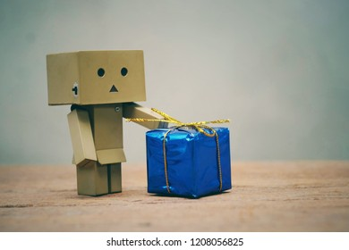 SAMUTSONGKHRAM, THAILAND - OCTOBER 21, 2018: Danbo or Danboard and small blue gift box on old wood table
