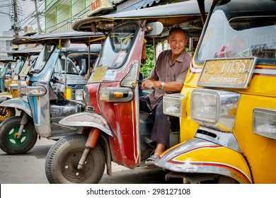 SAMUTSONGKRAM - THAILAND-AUG 25:A three wheeled tuk tuk taxi and driver smiling on August 25,2008 in Samutsongkram,Thailand. Tuk tuks are commonly used in transporting people and goods around the city
