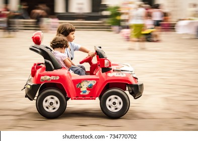 San Agustin, Colombia - December 15 2012: Boy and girl speeding over a market place in a toy car in Colombia.