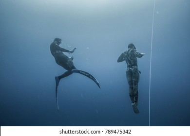 SAN ANDRES ISLAND, Colombia _ Circa March 2017. Freediver and his Safety Diver Diving and Following the Life Line at all time in the Deep Blue of San Andres Island, Colombia.