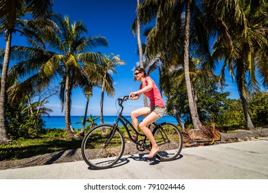 SAN ANDRES ISLAND, Colombia _ Circa March 2017. Woman Bicycling Bare Foot in the Street in the Caribbean