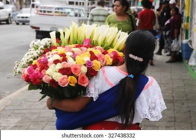 SAN ANDRES TUXTLA, MEXICO - JANUARY 17,2015: Maya woman carrying flowers at the Zocalo on January 17,2015 in San Andres Tuxtla
