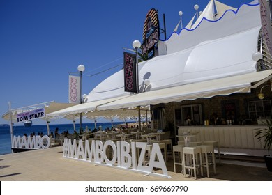 SAN ANTONIO, IBIZA, SPAIN - 13 JUNE 2017 - Tourists enjoying a meal in the daytime at popular Cafe Mambo Ibiza. Banner sign advertising an event for the DJ Tom Staar.