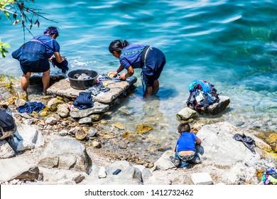 San Antonio Palopo, Lake Atitlan, Guatemala - March 20, 2019: Indigenous Maya ladies wash laundry at lakeside, San Antonio  Palopo, Lake Atitlan in Guatemalan highlands.