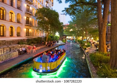 San Antonio, Texas - April 18, 2018: Boats pass through the river with pedestrians on the walkways of the River Walk in downtown San Antonio at twilight.