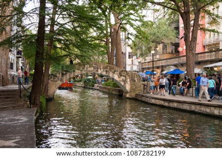 San Antonio, Texas - April 19, 2018: Boat tours cruise the river while people shop and eat at restaurants along the walkways of the River Walk in downtown San Antonio.