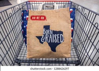 """SAN ANTONIO, TEXAS - NOVEMBER 9, 2018 - Shopping cart with H-E-B reusable shopping bag with the Texas state outline and the words """"Born & Raised"""". HEB is an American privately held supermarket chain."""