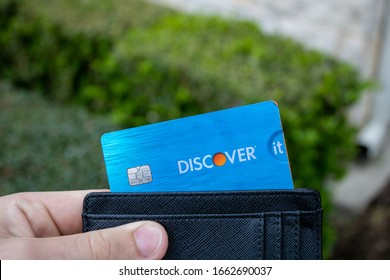San Antonio, TX / USA - Mar. 03, 2020: A hand and wallet holds a Discover It Student Miles credit card, which gives users points towards travel credit and Priority Pass airport lounge access.