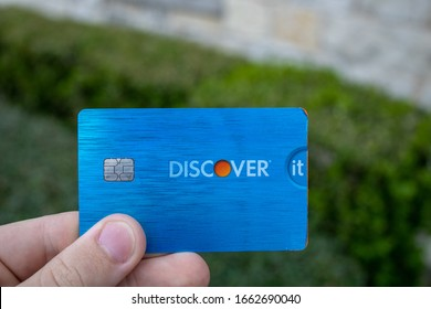 San Antonio, TX / USA - Mar. 03, 2020: A hand holds a Discover It Student Miles credit card, which gives users points towards travel credit and Priority Pass airport lounge access.