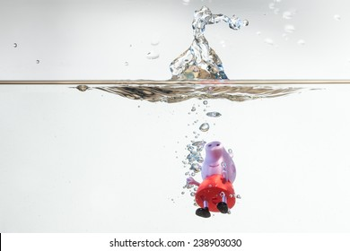 SAN BENEDETTO DEL TRONTO, ITALY. DECEMBER 1, 2014. Peppa Pig doll fall in water with splash. Peppa pig is a english cartoon that is famous all over the world. White background