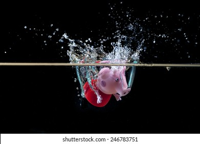 SAN BENEDETTO DEL TRONTO, ITALY. DECEMBER 1, 2014. Peppa Pig doll fall in water with splash. Peppa pig is a english cartoon that is famous all over the world. Blackbackground