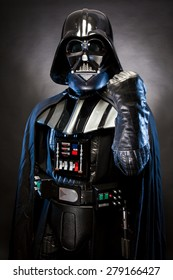 SAN BENEDETTO DEL TRONTO, ITALY. MAY 16, 2015. Half-lenght portrait of Darth Vader with fist punch . Lord Fener is a fictional character of Star Wars saga. Black background. Blue grazing light