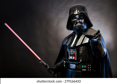 SAN BENEDETTO DEL TRONTO, ITALY. MAY 16, 2015. Portrait of Darth Vader costume replica with grab hand and his sword . Lord Fener is a fictional character of Star Wars saga. Black background.