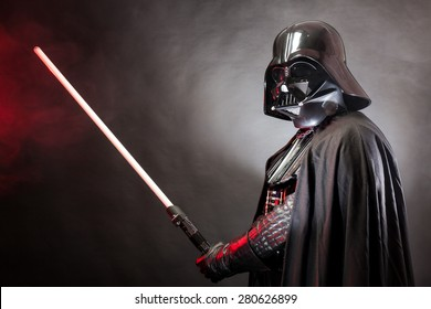 SAN BENEDETTO DEL TRONTO, ITALY. MAY 16, 2015. Portrait of Darth Vader costume replica with  his sword . Darth Vader is a fictional character of Star Wars saga.  Red grazing light and black background