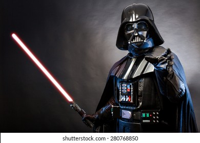 SAN BENEDETTO DEL TRONTO, ITALY. MAY 16, 2015. Portrait of Darth Vader costume replica with grab hand and his sword . Lord Fener is a fictional character of Star Wars saga.  Blue grazing light