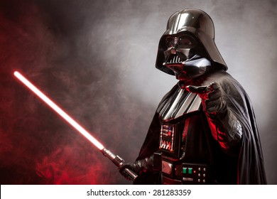 SAN BENEDETTO DEL TRONTO, ITALY. MAY 16, 2015. Portrait of Darth Vader costume replica with grab hand and his red sword. Lord Fener is a fictional character of Star Wars saga. Red backlight and smoke