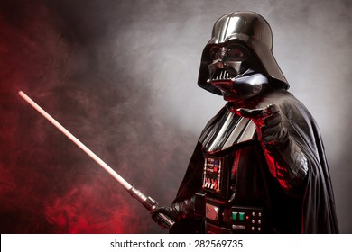 SAN BENEDETTO DEL TRONTO, ITALY. MAY 16, 2015. Portrait of Darth Vader costume replica with grab hand and  sword . Lord Fener is a fictional character of Star Wars saga.  Red grazing light and smoke