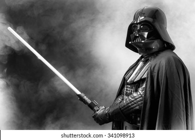 SAN BENEDETTO DEL TRONTO, ITALY. MAY 16, 2015. Portrait of Darth Vader costume replica with  sword . Lord Fener is a fictional character of Star Wars saga.  Black and white picture, smoke background