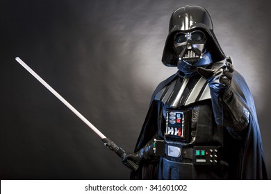 SAN BENEDETTO DEL TRONTO, ITALY. MAY 16, 2015. Portrait of Darth Vader costume replica with grab hand and  sword . Lord Fener is a fictional character of Star Wars saga.  Blue grazing light