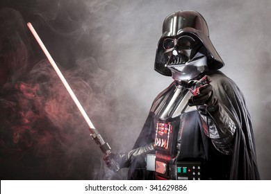 SAN BENEDETTO DEL TRONTO, ITALY. MAY 16, 2015. Portrait of Darth Vader costume replica with grab hand and  sword . Darth Vader is a fictional character of Star Wars saga.  Red grazing light and smoke