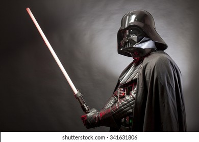 SAN BENEDETTO DEL TRONTO, ITALY. MAY 16, 2015. Portrait of Darth Vader costume replica with his sword . Darth Vader is a fictional character of Star Wars saga.  Black background