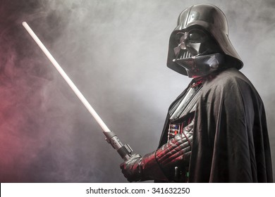 SAN BENEDETTO DEL TRONTO, ITALY. MAY 16, 2015. Portrait of Darth Vader costume replica with his sword . Lord Fener is a fictional character of Star Wars saga.  Red backlight and smoke