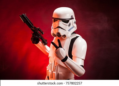 SAN BENEDETTO DEL TRONTO, ITALY. NOVEMBER 11, 2017. Studio portrait  of stormtrooper costume replica, with V sign hand and blaster gun. He is a fictional character of Star Wars saga. Red background