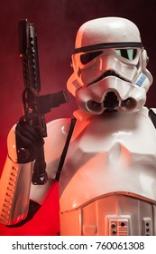 SAN BENEDETTO DEL TRONTO, ITALY. NOVEMBER 11, 2017. Studio portrait  of stormtrooper costume replica, with blaster E-11 gun. He is a fictional character of Star Wars saga. Red background