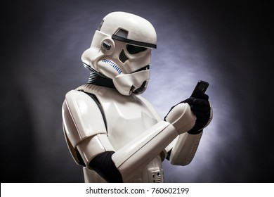 SAN BENEDETTO DEL TRONTO, ITALY. NOVEMBER 11, 2017. Funny studio portrait  of stormtrooper costume replica with a mobile phone . He is a fictional character of Star Wars saga. Black background