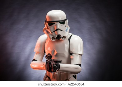 SAN BENEDETTO DEL TRONTO, ITALY. NOVEMBER 11, 2017. Studio portrait  of stormtrooper costume replica, with blaster E-11 gun. He is a fictional character of Star Wars saga. Black background with smoke
