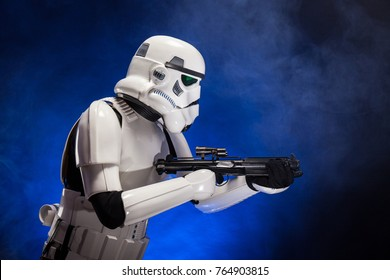 SAN BENEDETTO DEL TRONTO, ITALY. NOVEMBER 11, 2017. Profile studio portrait  of stormtrooper costume replica, with blaster E-11 gun. He is a fictional character of Star Wars saga. Blue background