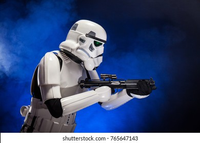 SAN BENEDETTO DEL TRONTO, ITALY. NOVEMBER 11, 2017. Studio portrait  of stormtrooper costume replica, with blaster E-11 gun. He is a fictional character of Star Wars saga. Blue background with smoke