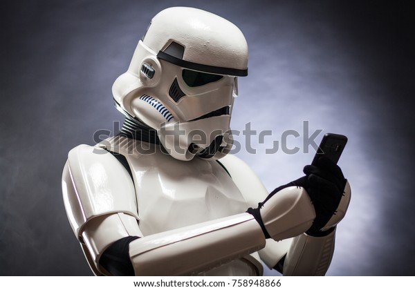 SAN BENEDETTO DEL TRONTO, ITALY. NOVEMBER 11, 2017. Funny studio portrait  of stormtrooper costume replica with a mobile phone . He is a fictional character of Star Wars saga. Blue background