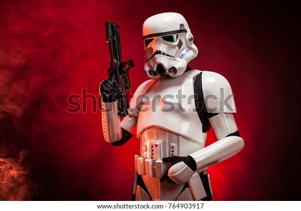 SAN BENEDETTO DEL TRONTO, ITALY. NOVEMBER 11, 2017. Studio portrait  of stormtrooper costume replica, with blaster E-11 gun. He is a fictional character of Star Wars saga. Red background with smoke