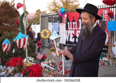 SAN BERNARDINO, CA - DECEMBER 6: Jewish rabbi lights first Hanukkah candle at a makeshift memorial to IRC shooting victims on December 6, 2015 in San Bernardino, California.