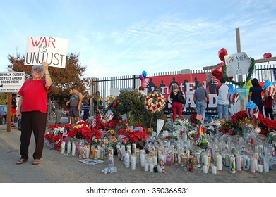 SAN BERNARDINO, CA - DECEMBER 6: A woman demonstrates while people visit a makeshift memorial to IRC shooting victims on December 6, 2015 in San Bernardino, California.