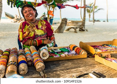 San Blas Islands, Panama. March 2018. A view of a Kuna lady wearing traditional mola, making traditional, chaquiras , on Isla Banderas, in the san Blas, Panama.