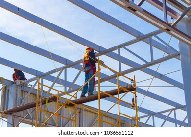 San Blas, Nayart / Mexico - February 12 2018: A man works safely harnessed to the beams of the structure. In this country, work regulations are needed to work in heights.