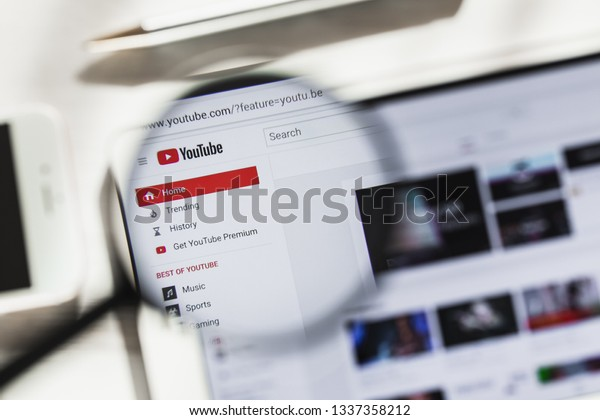 San Bruno, California, USA - 14 March 2019: YouTube Video hosting, social official website homepage under magnifying glass. Concept YouTube, social network logo visible on smartphone, tablet screen