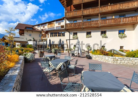 SAN CASSIANO, DOLOMITES, ITALY - SEP 25, 2013: chairs with table on sunny terrace of alpine luxury restaurant and hotel in San Cassiano village. Wealthy tourists visit northern part of Italy in autumn