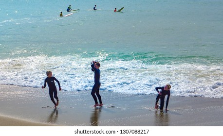 San Clemente, CA / USA - Feb. 2 2019: Teen Surfers Playing at Shoreline