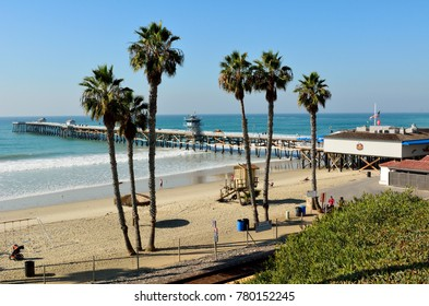 San Clemente, California, United States of America - December 1, 2017. View of San Clemente pier and T-Street beach, with palm trees, people and commercial properties.