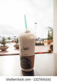 San Clemente, California, USA - 05 12 2017: Starbucks vanilla coffee Frappucino, an unhealthy blended coffee beverage with milk, ice, sugar and whipped cream in disposable plastic drink cup with straw