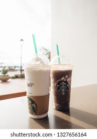 San Clemente, California, USA - 05 12 2017: Starbucks vanilla coffee and chocolate mocha mint Frappucino, blended coffee beverages with ice and whipped cream in disposable plastic drink cup with straw