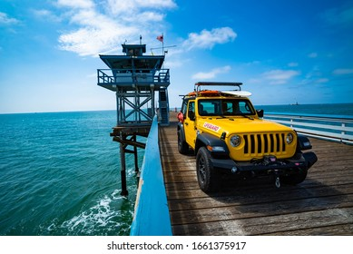 San Clemente, California / USA - September 16 2019: Picturesque yellow lifeguard Jeep Wrangler beach vehicle parked on the San Clemente Pier on a bright sunny happy day with blue skies.