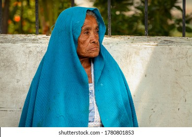 San Cristobal, Chiapas / Mexico - April 21, 2012: A sad old woman wearing a blue shawl watches and waits in a rural village in Mexico.