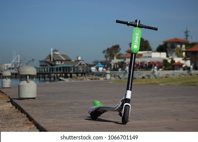 San Diego, CA / USA - April 10, 2018: A green Lime-S electric scooter is ready for the next person in San Diego's Embarcadero Marina Park, as the city embraces dockles ride sharing