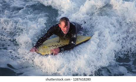 San Diego, CA / USA - December 19, 2018: Older man with wetsuit surfing a large wave on a boogie-board