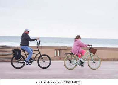 San Diego, CA USA - Jan 8 2021: Man and woman riding bicycles along the boardwalk at Mission Beach in the afternoon on a chilly day