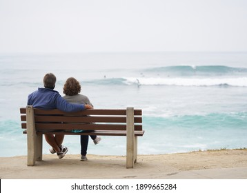 San Diego, CA USA - Jan 5 2021: Man and woman sit together on a park bench overlooking Windansea beach in San Diego watching the ocean waves